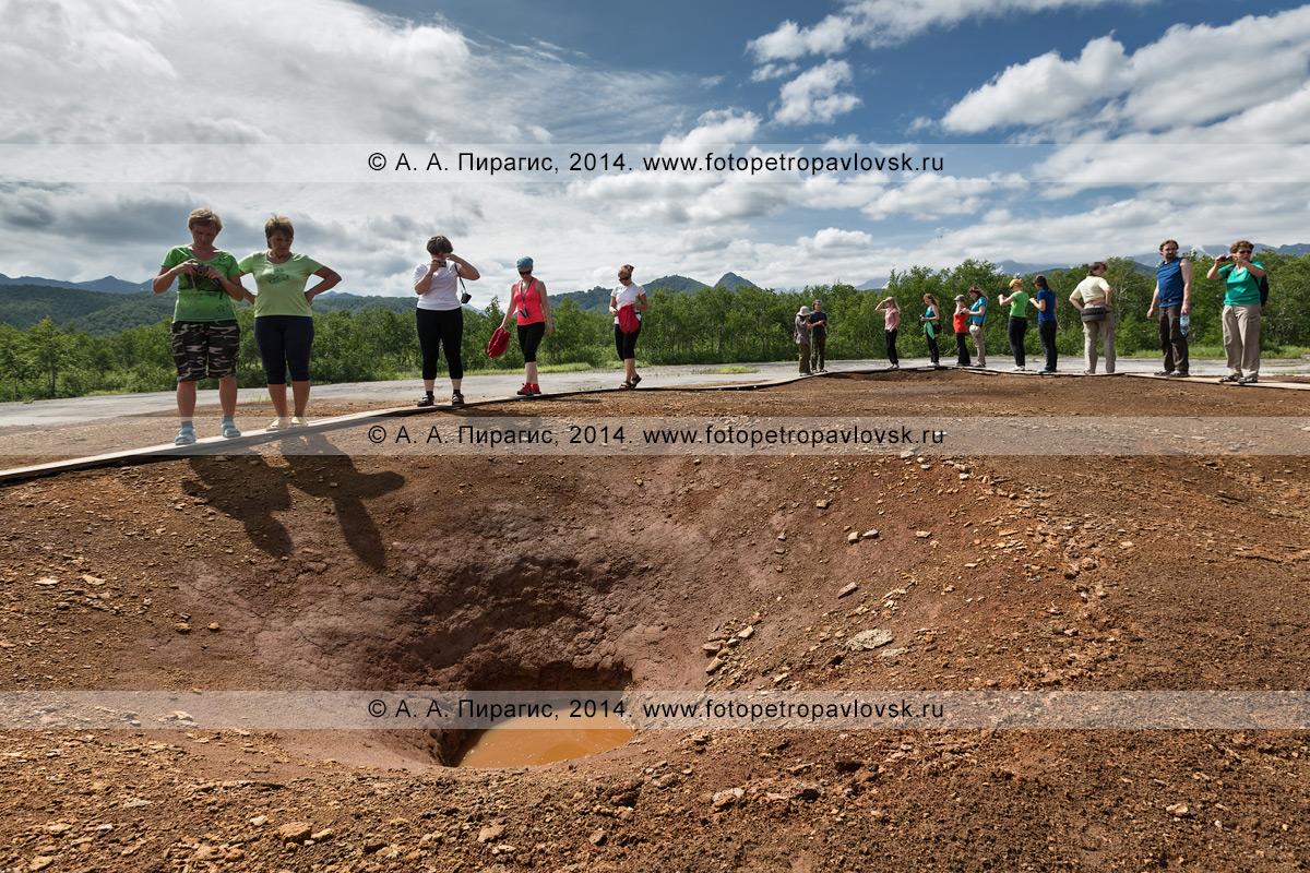 Термальная площадка Котел, или травертиновый щит Котел. Туристы и путешественники гуляют по деревянному настилу вокруг грифонов с термальной водой. Налычевская долина, полуостров Камчатка