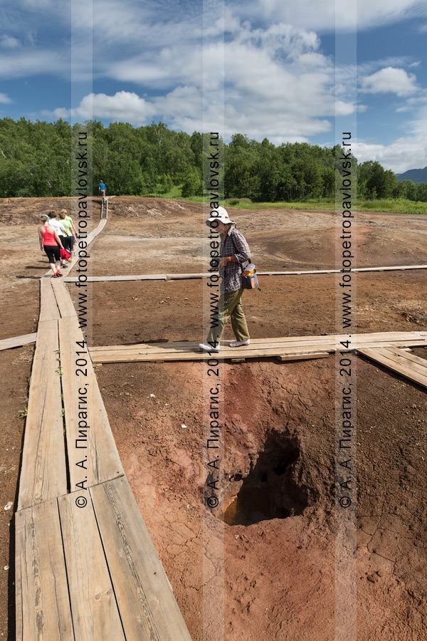 Туристы и путешественники прогуливаются по термальной площадке Котел (травертиновый щит Котел). Полуостров Камчатка, Налычево