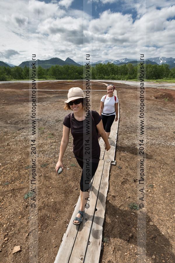 Туристки и путешественницы идут по деревянным мосткам на травертиновом щите Котел, или термальной площадке Котел. Камчатский край, Налычево