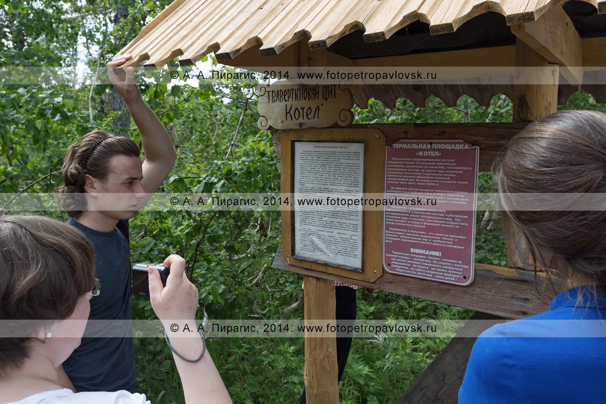 Туристы и путешественники знакомятся с информацией о термальной площадке Котел (травертиновый щит Котел) в Налычево на Камчатке, размещенной на информационном стенде (щит, аншлаг) под деревянным навесом