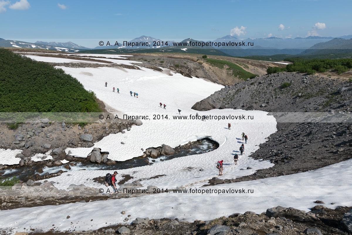 Туристическая группа переправляется через горную реку по снежнику. Налычево, Камчатка