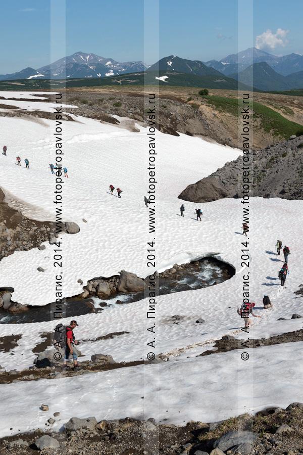Туристы и путешественники преодолевают водную преграду (реку) по снежному мосту (снежнику). Налычевская долина, Камчатка