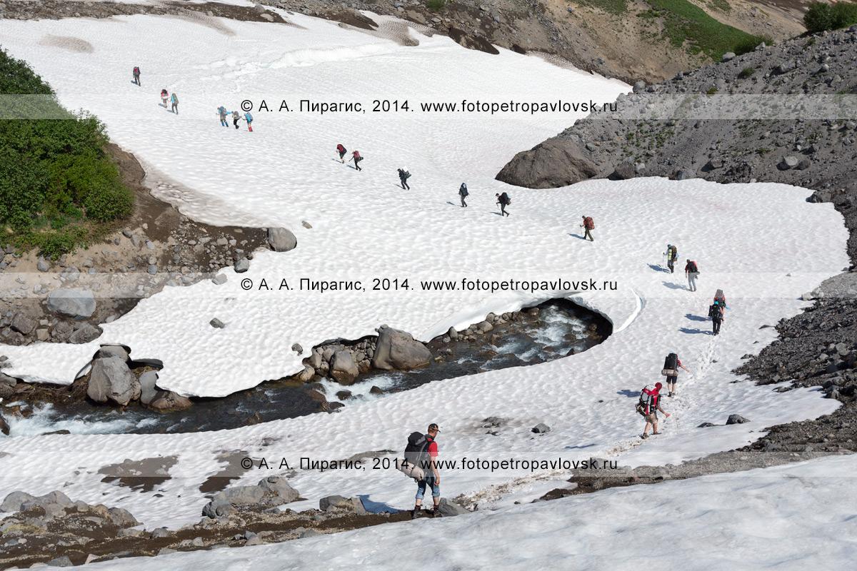 Группа туристов и путешественников идет по снежнику через горную реку. Камчатский край, Налычевская долина