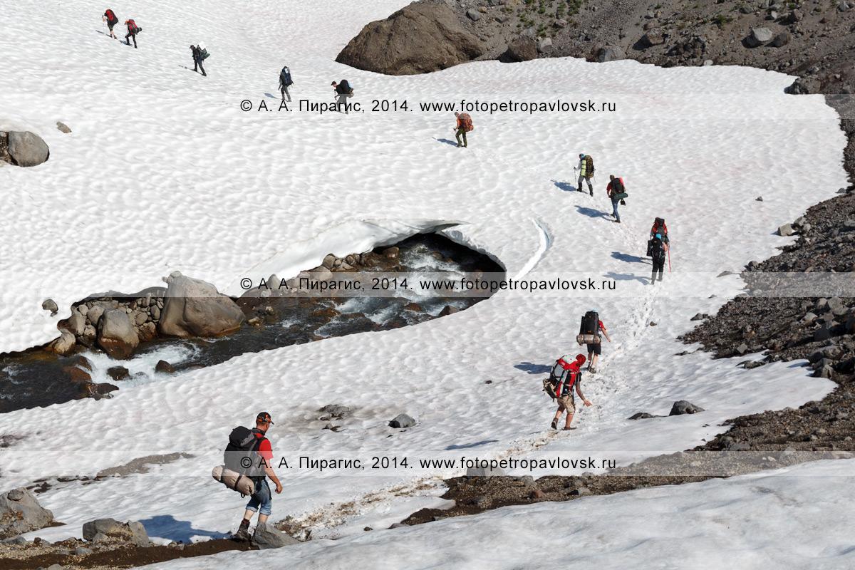 Туристы и путешественники идут по снежному мосту (снежнику) через бурную горную речку. Камчатка, Налычевский природный парк