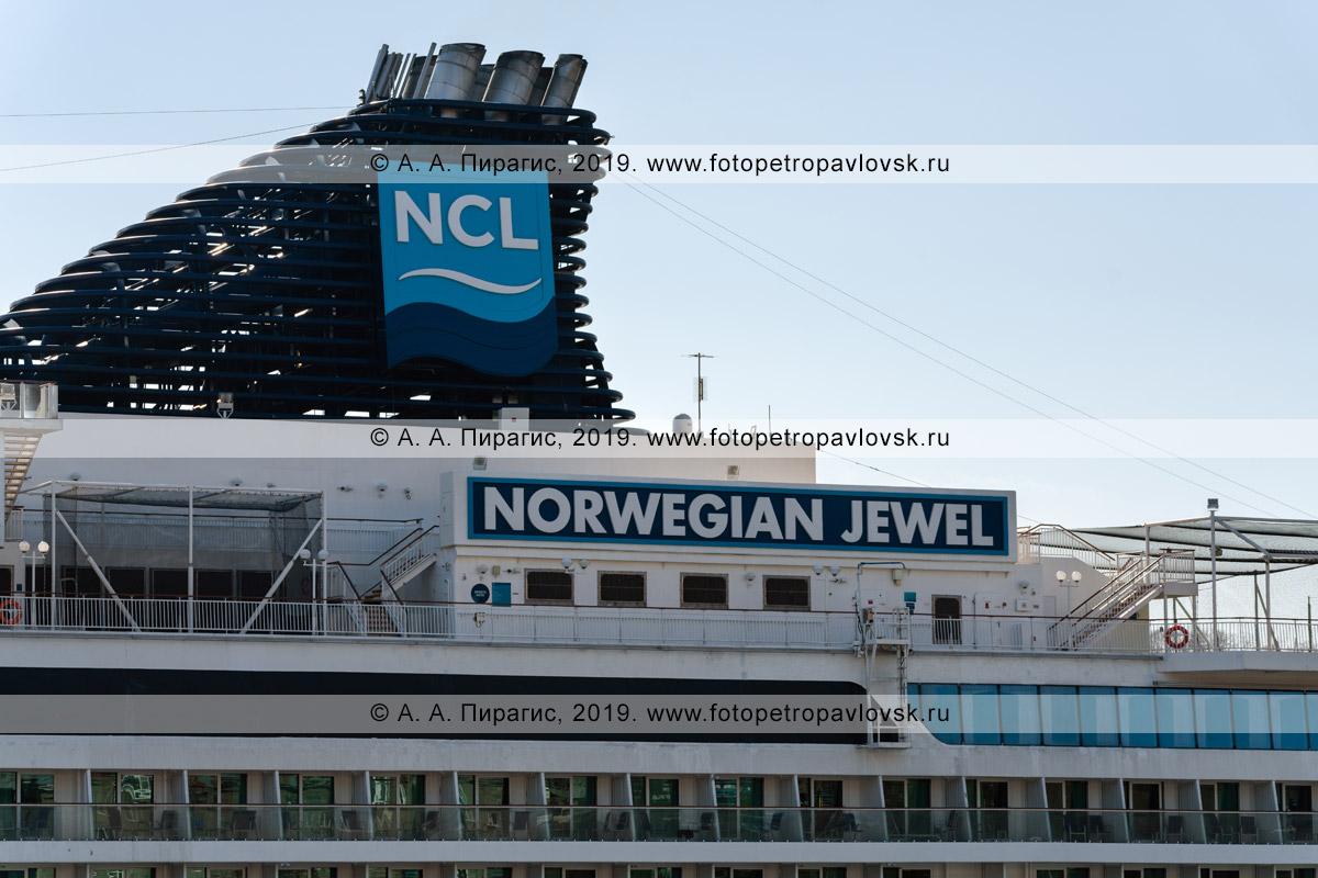 Фотография: вид на дымовые трубы возвышающиеся над надстройками круизного судна Norwegian Jewel, логотип компании Norwegian Cruise Line и название круизного лайнера