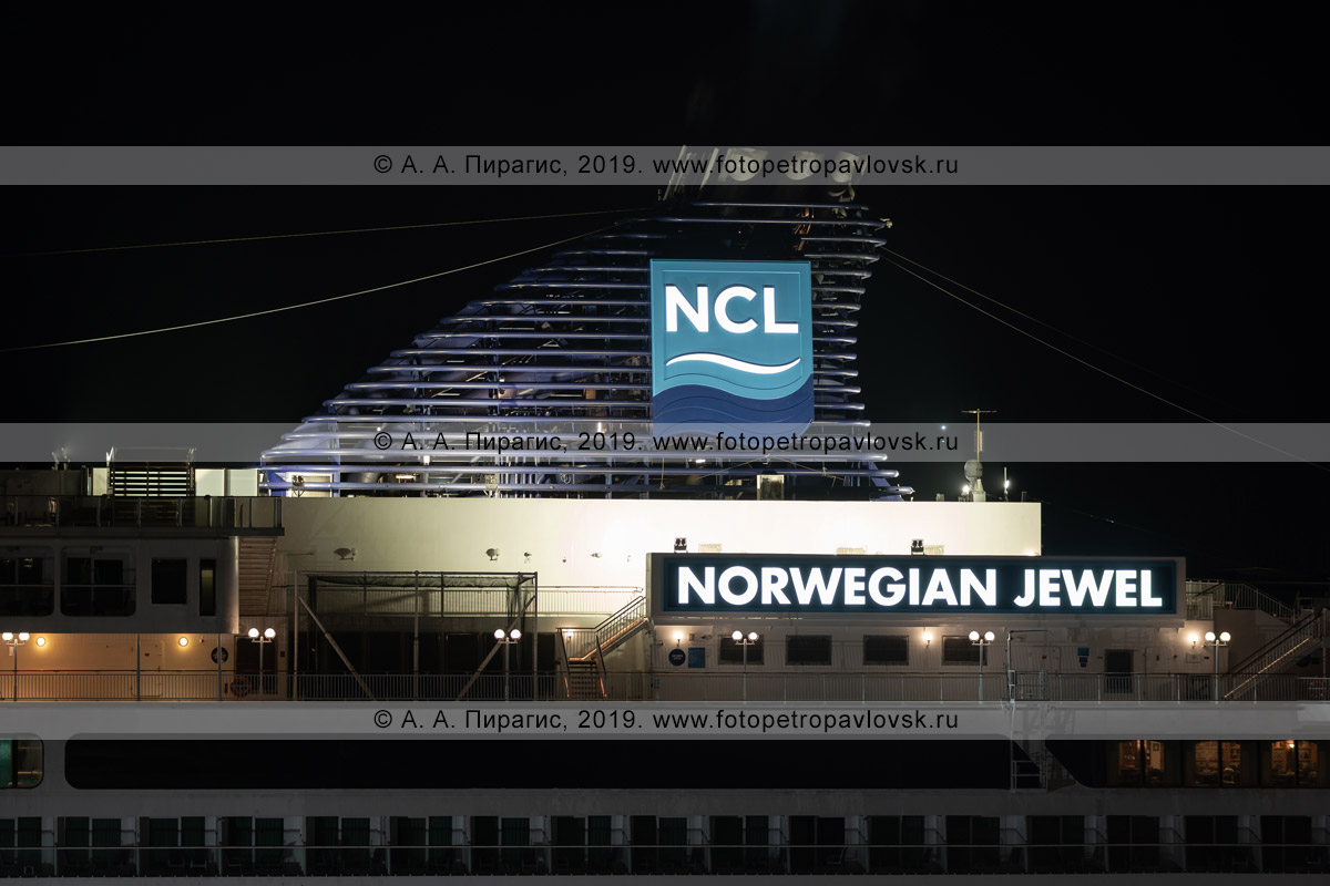 Фотография: ночной вид на подсвеченные дымовые трубы, возвышающиеся над надстройками круизного судна, святящийся в ночи логотип компании Norwegian Cruise Line и название круизного лайнера Norwegian Jewel