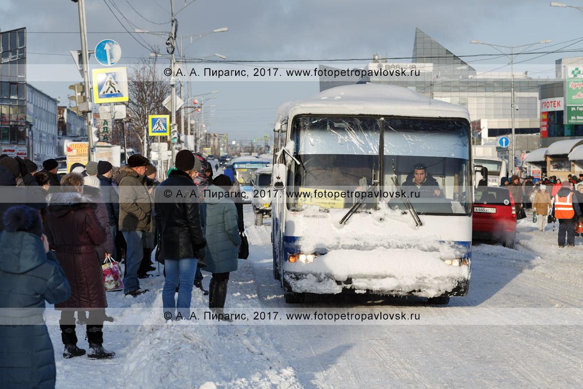 Фотография: зимний городской пейзаж Петропавловска-Камчатского после снежного циклона (пурги, метели) — люди в ожидании общественного транспорта стоят на проезжей части в районе автобусной остановки, не полностью расчищенной после непогоды
