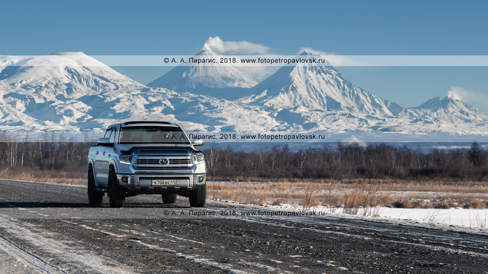 Фотография: японский внедорожник Toyota Tundra едет по автодороге на фоне камчатского зимнего пейзажа — вулканов Ключевской группы