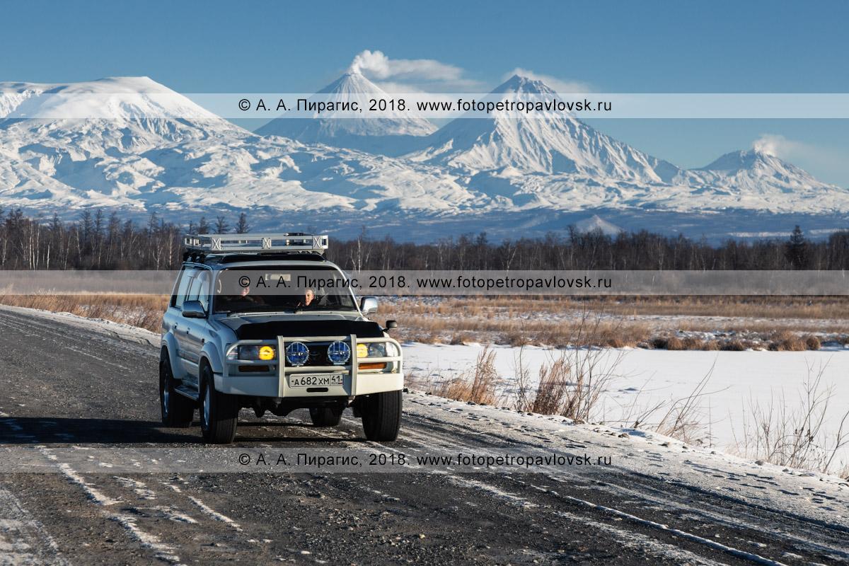 Фотография: японский внедорожник Toyota Land Cruiser едет по шоссе на фоне зимнего пейзажа полуострова Камчатка — величественной Ключевской группы вулканов