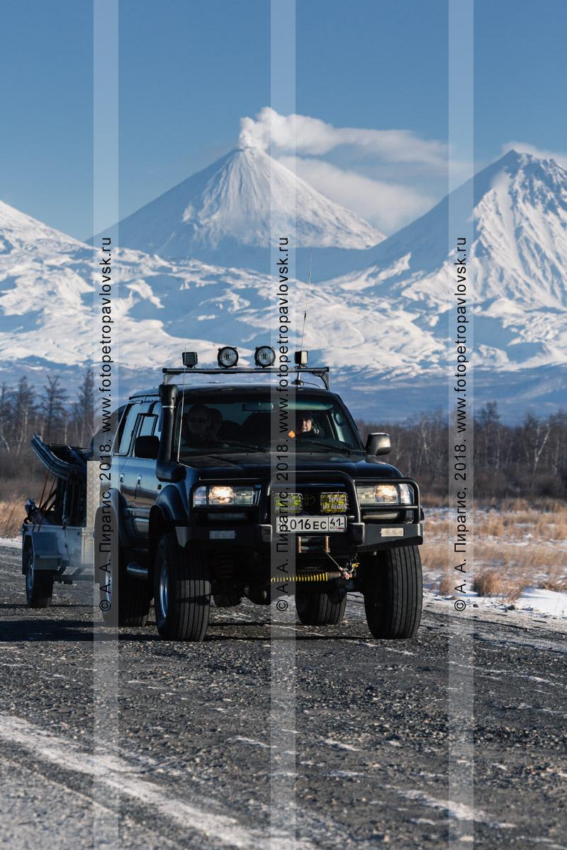 Фотография: японский внедорожник Toyota Land Cruiser едет по автотрассе на фоне зимнего пейзажа Камчатского края