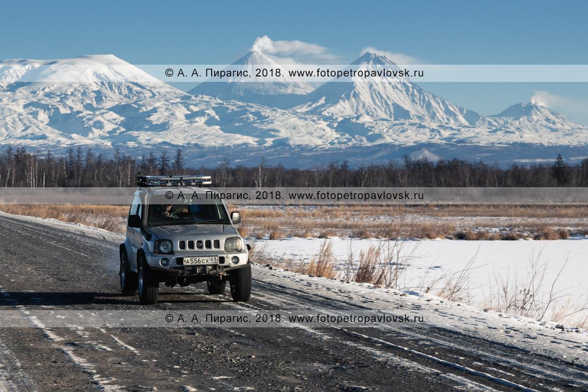Фотография: японский автомобиль Suzuki Jimny едет по зимней автотрассе на фоне Ключевской группы вулканов — вулкан Ушковский, вулкан Ключевской, вулкан Камень и вулкан Безымянный
