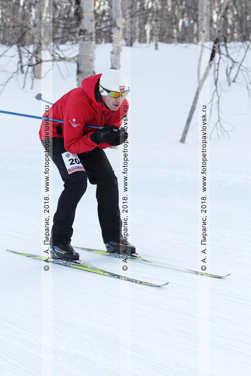 """Мужчина-лыжник едет с горы на лыжах. Всероссийская массовая лыжная гонка """"Лыжня России"""". Полуостров Камчатка, город Петропавловск-Камчатский"""
