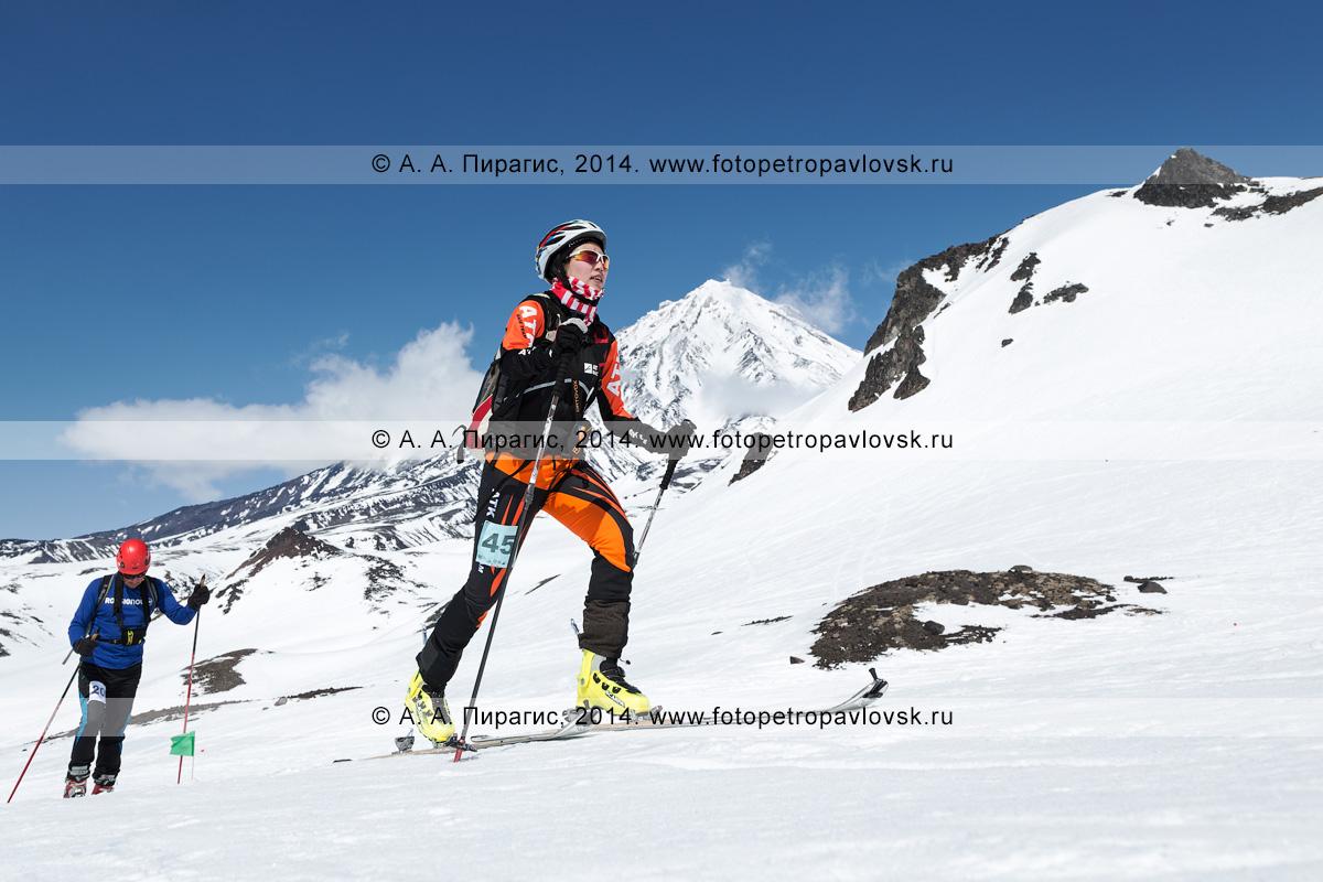 Фотография: китайская ски-альпинистка Ma Nan поднимается на лыжах с пристегнутым камусом на Авачинский вулкан на фоне Корякского вулкана. Соревнования по ски-альпинизму — индивидуальная гонка. Камчатка