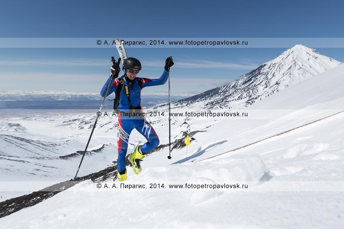 Фотография: камчатский ски-альпинист Баранов Денис поднимается пешком (с лыжами, пристегнутыми к рюкзаку) на Авачинский вулкан на фоне Корякского вулкана. Соревнования по ски-альпинизму — индивидуальная гонка. Полуостров Камчатка