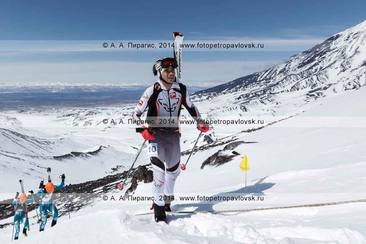 Фотография: камчатский ски-альпинист Загорский Алексей поднимается пешком (с лыжами, пристегнутыми к рюкзаку) на вулкан Авачинская сопка на Камчатке. Соревнования по ски-альпинизму — индивидуальная гонка