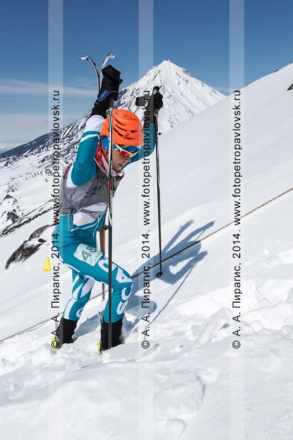Фотография: камчатская ски-альпинистка Екатерина Осичкина поднимается пешком (с лыжами, пристегнутыми к рюкзаку) на Авачинский вулкан на фоне Корякского вулкана. Соревнования по ски-альпинизму — индивидуальная гонка. Камчатка