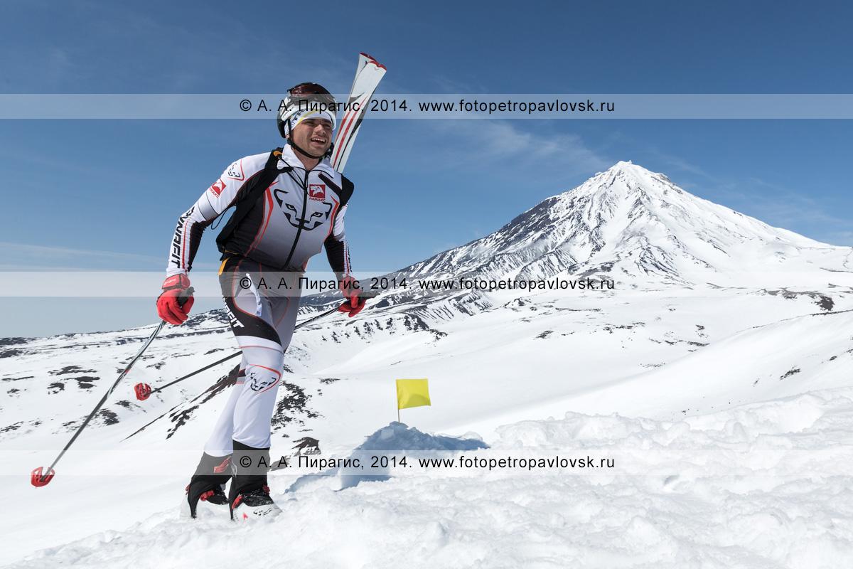 Фотография: камчатский ски-альпинист Загорский Алексей взбирается пешком (с лыжами, пристегнутыми к рюкзаку) на Авачинский вулкан на фоне Корякского вулкана. Соревнования по ски-альпинизму — индивидуальная гонка. Камчатский край