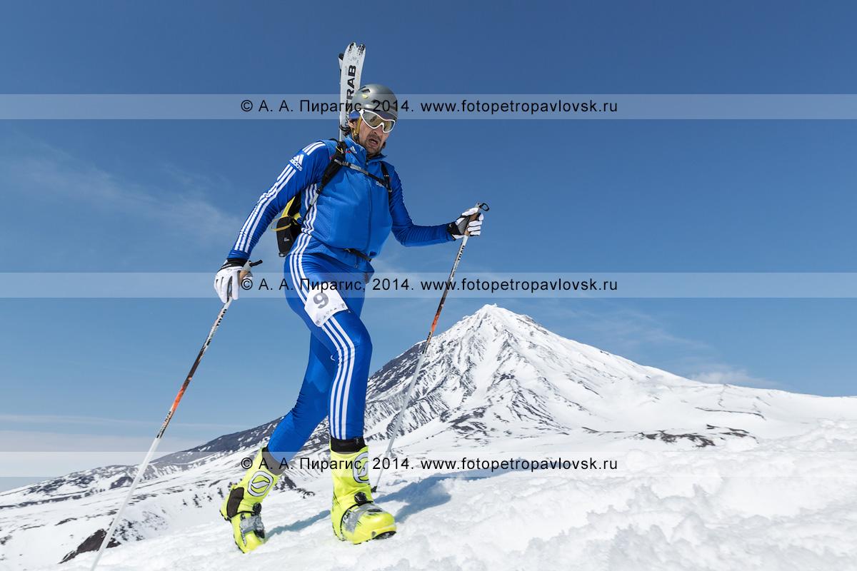 Фотография: камчатский ски-альпинист Владимир Амангалиев поднимается пешком (с лыжами, пристегнутыми к рюкзаку) на вулкан Авачинский на фоне вулкана Корякский. Соревнования по ски-альпинизму — индивидуальная гонка. Полуостров Камчатка