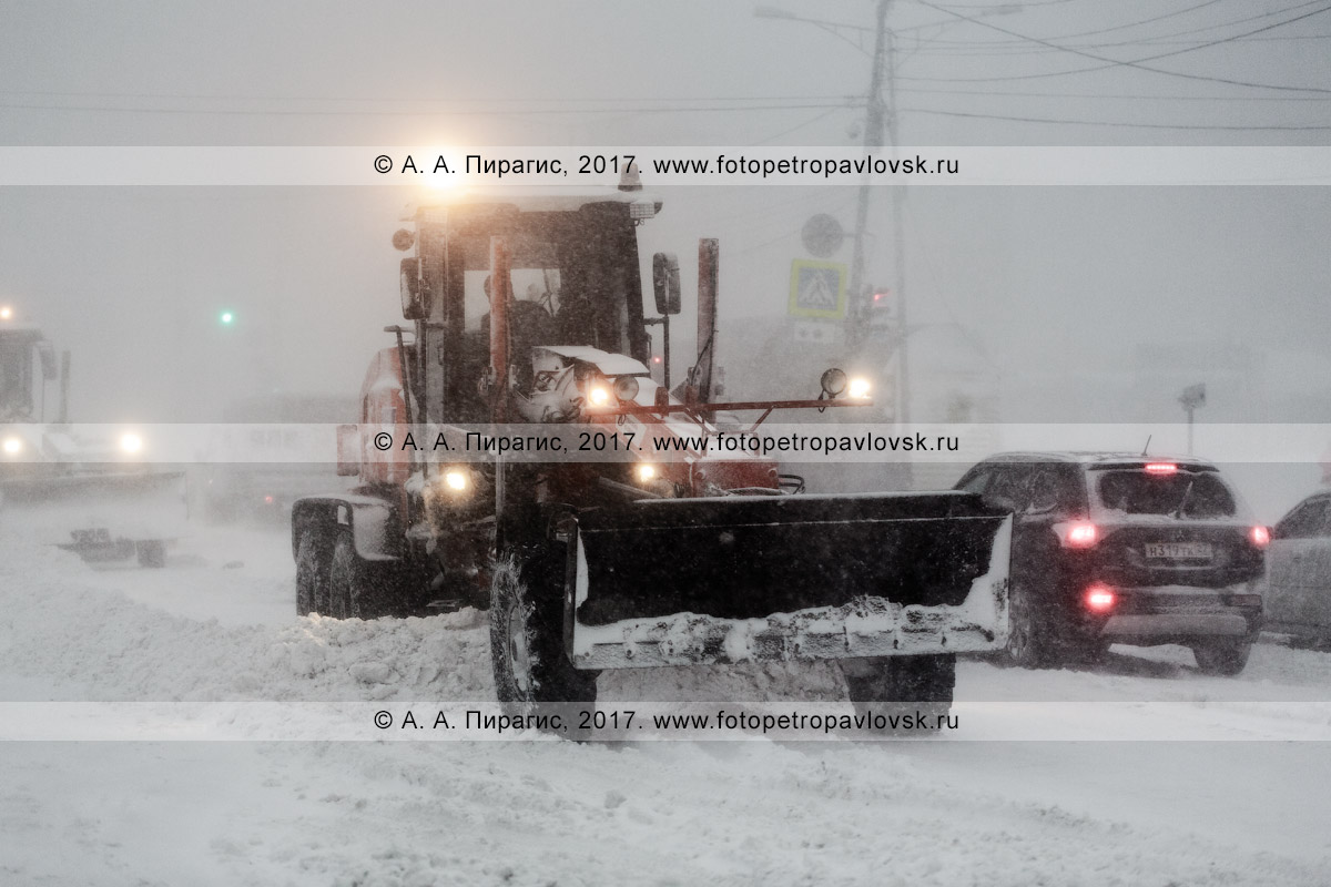 Фотография: снегоуборочная техника — грейдер чистит автодорогу во время пурги (метели) в городе Петропавловске-Камчатском