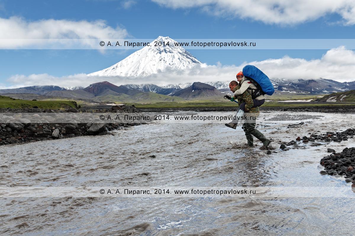 Фотография: пеший туризм на полуострове Камчатка — гид переносит девушку-туристку с рюкзаком за плечами через горную реку Студеную