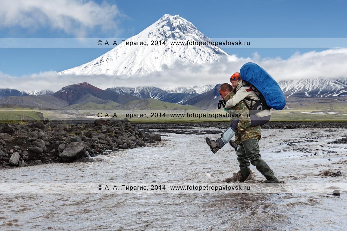 Фотография: пеший туризм на Камчатке — гид переносит девушку-туристку (с рюкзаком за плечами) через горную реку Студеную