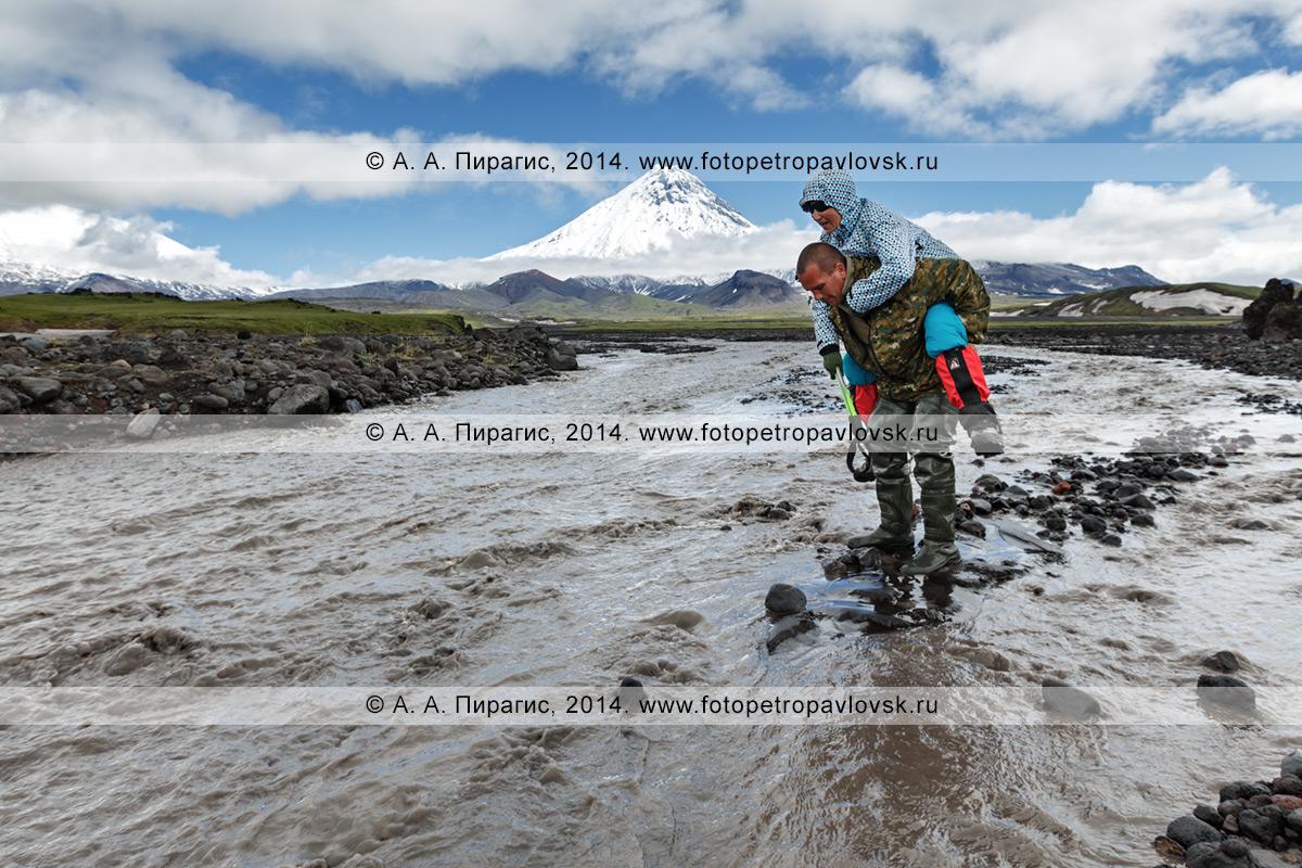 Фотография: пеший туризм по Камчатскому краю — гид переносит девушку-туристку через горную реку Студеную (река Студенка)