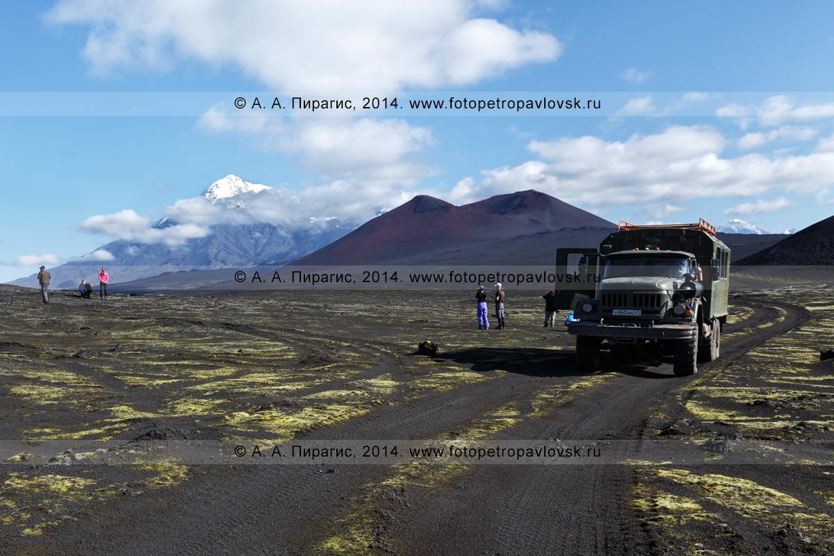 Фотография: туристы и путешественники возле экспедиционного автомобиля высокой проходимости ЗИЛ-131 (вахтовка) на Толбачинском долу на фоне вулкана Острый Толбачик и шлаковых конусов. Камчатский край