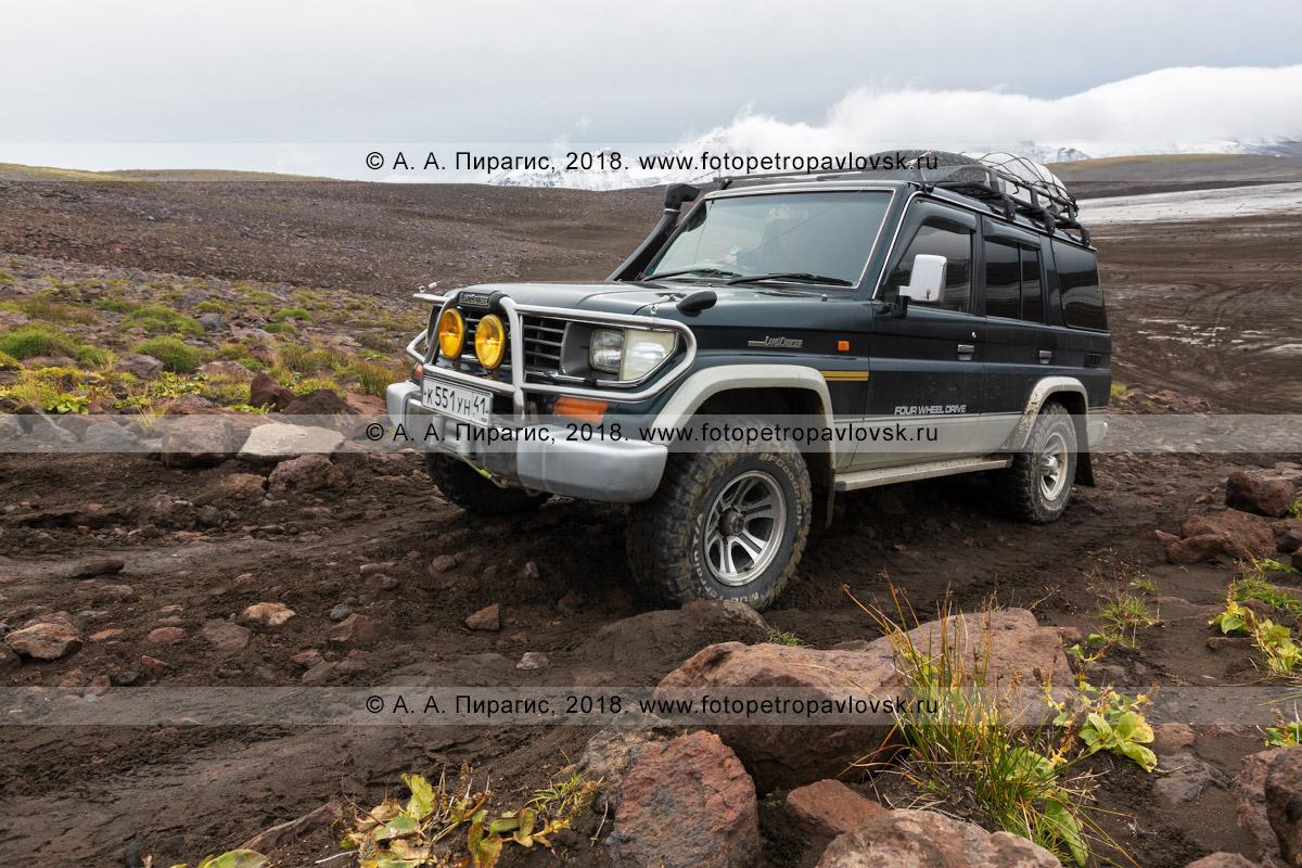 Фотография: автомобиль Toyota Land Cruiser Prado взбирается по грунтовой дороге из кальдеры вулкана Горелого