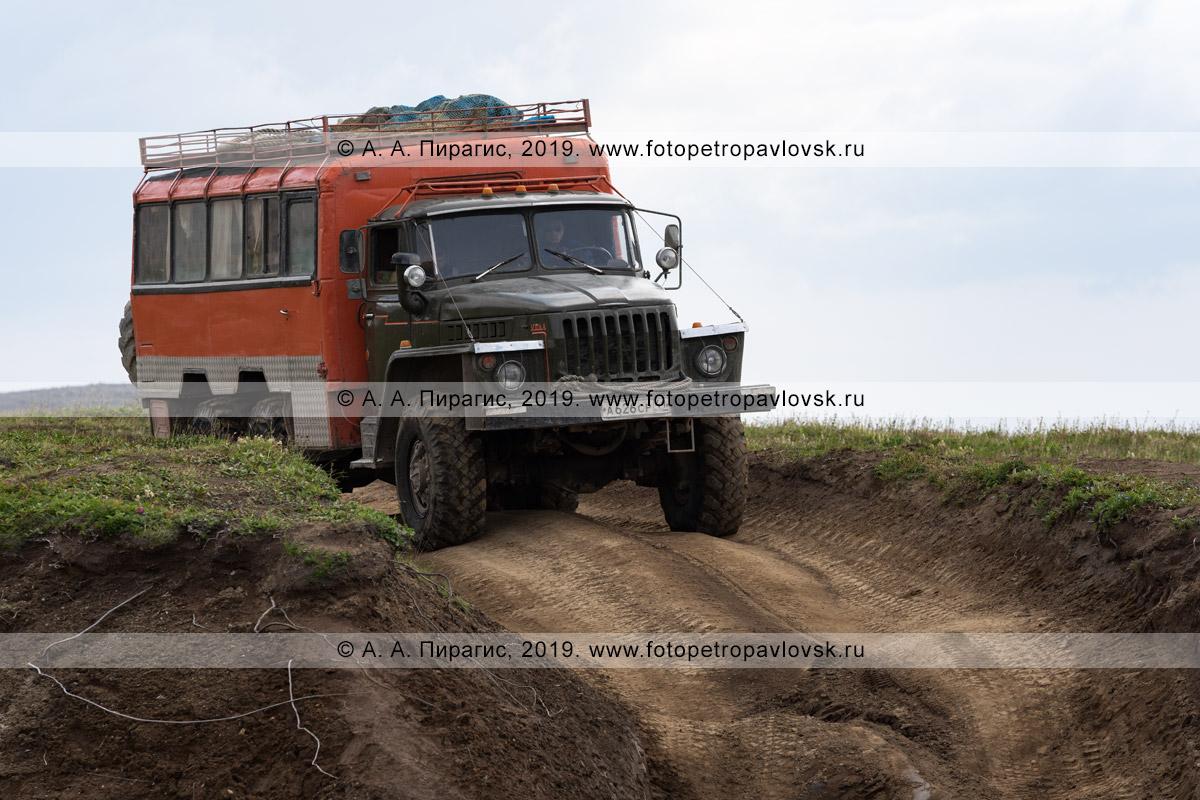 Фотография: вахтовка Урал везет туристов и путешественников по проселочной грунтовой дороге в горах
