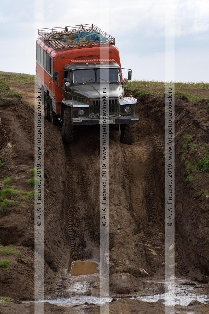 Фотография: вахтовый автобус Урал повышенной проходимости везет туристов и путешественников в кузове-фургоне по грунтовой дороге в камчатских горах