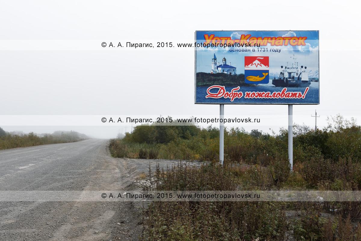 """Фотография: баннер (плакат, аншлаг), установленный возле автомобильной дороги, с приветственной надписью: """"Усть-Камчатск основан в 1731 году. Добро пожаловать!"""". Камчатский край, Усть-Камчатский район"""