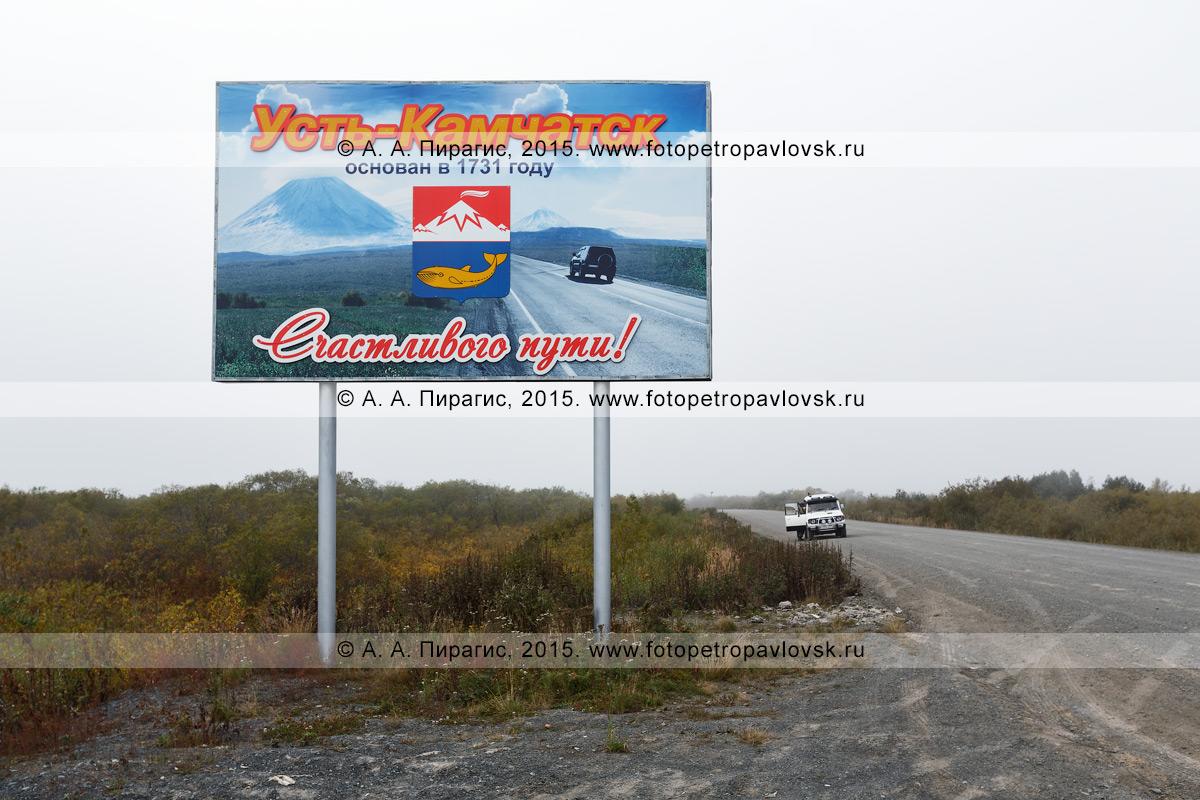 """Фотография: баннер (аншлаг, плакат), установленный возле автомобильной дороги, с надписью: """"Усть-Камчатск основан в 1731 году. Счастливого пути!"""". Усть-Камчатский район, Камчатка"""