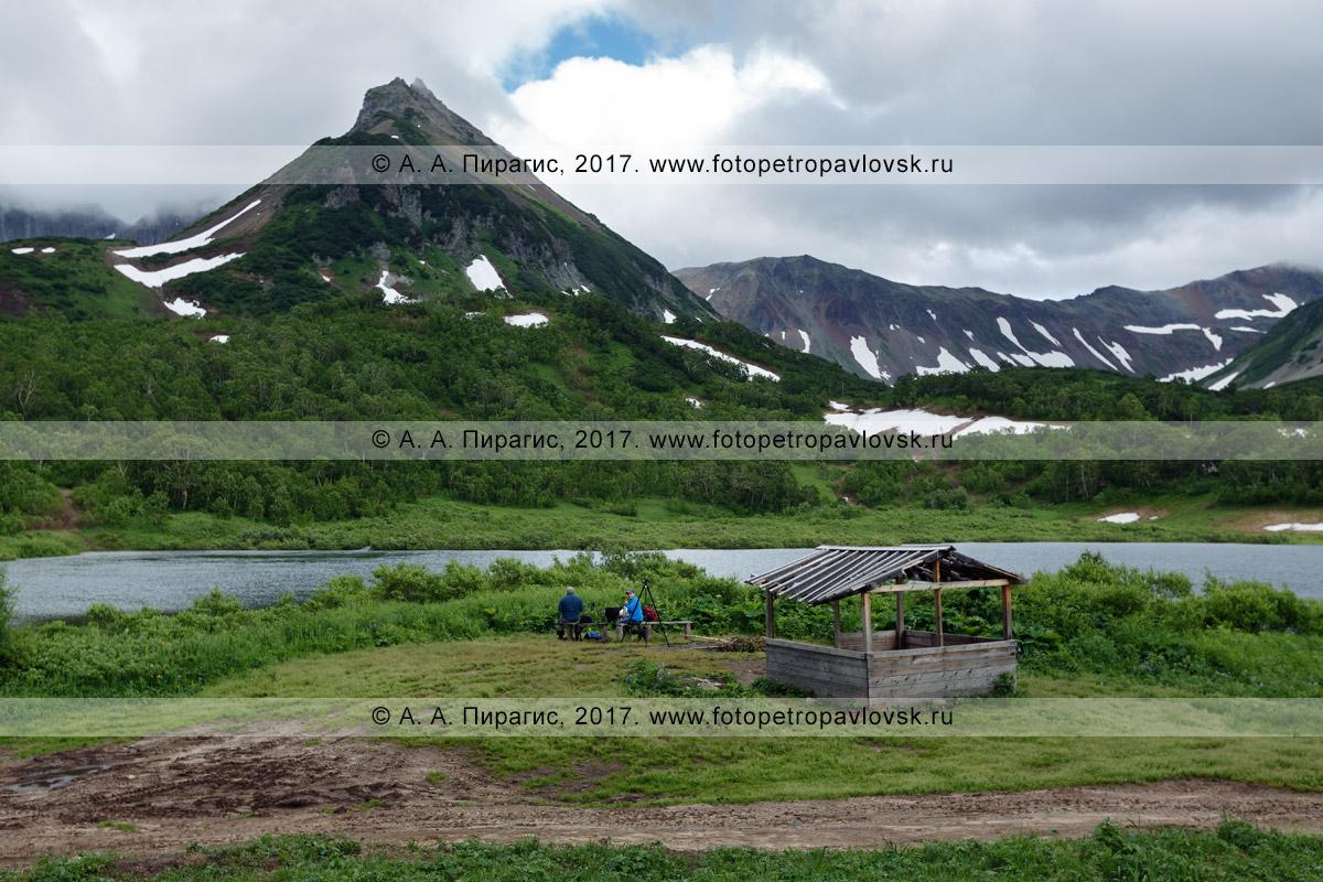 Фотография: деревянный навес (беседка) для отдыха туристов и путешественников, расположенный на берегу живописного озера Тахколоч в горном массиве Вачкажец на полуострове Камчатка