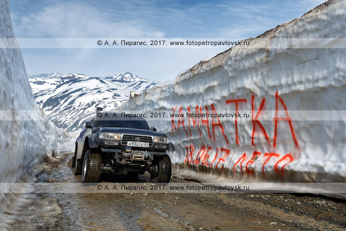 Фотография: японский полноприводный автомобиль Toyota Land Cruiser (с прицепом, везущим снегоход) едет по горной дороге в многометровом снежном тоннеле на Вилючинском перевале на полуострове Камчатка