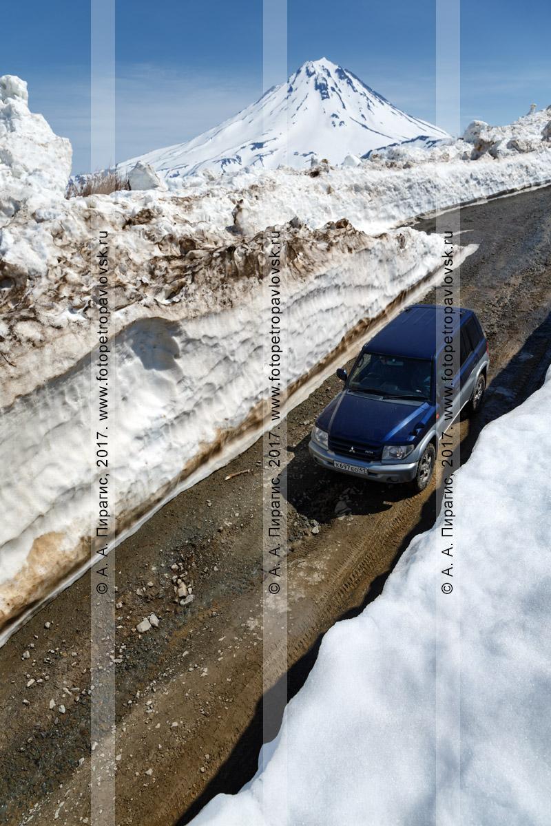 Фотография: полноприводный японский автомобиль Mitsubishi Pajero iO едет по горной дороге через многометровый снежный тоннель на Вилючинском перевале на полуострове Камчатка