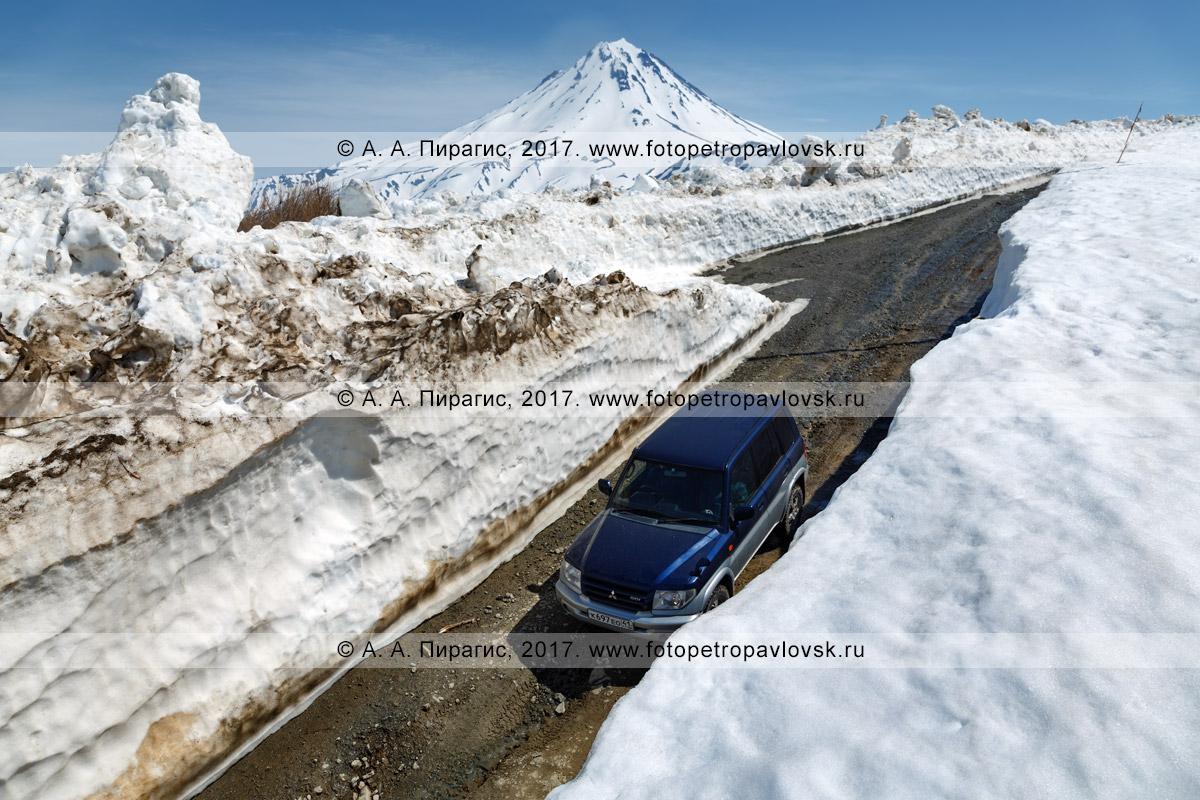 Фотография: полноприводный японский автомобиль Mitsubishi Pajero iO едет по горной дороге через многометровый снежный тоннель на Вилючинском перевале в Камчатском крае
