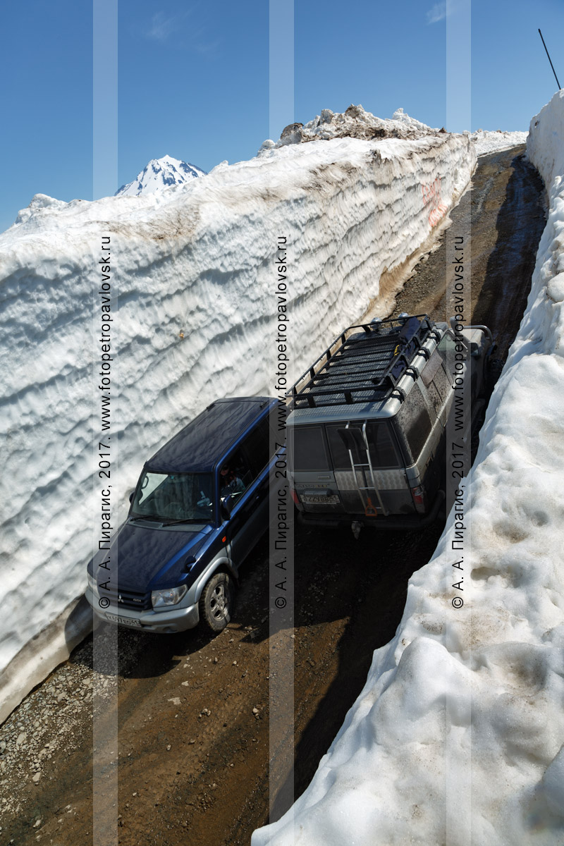 Фотография: японские полноприводные автомобили Mitsubishi Pajero iO и Toyota Land Cruiser Prado разъезжаются на узкой горной дороге в многометровом снежном тоннеле на Вилючинском перевале на полуострове Камчатка