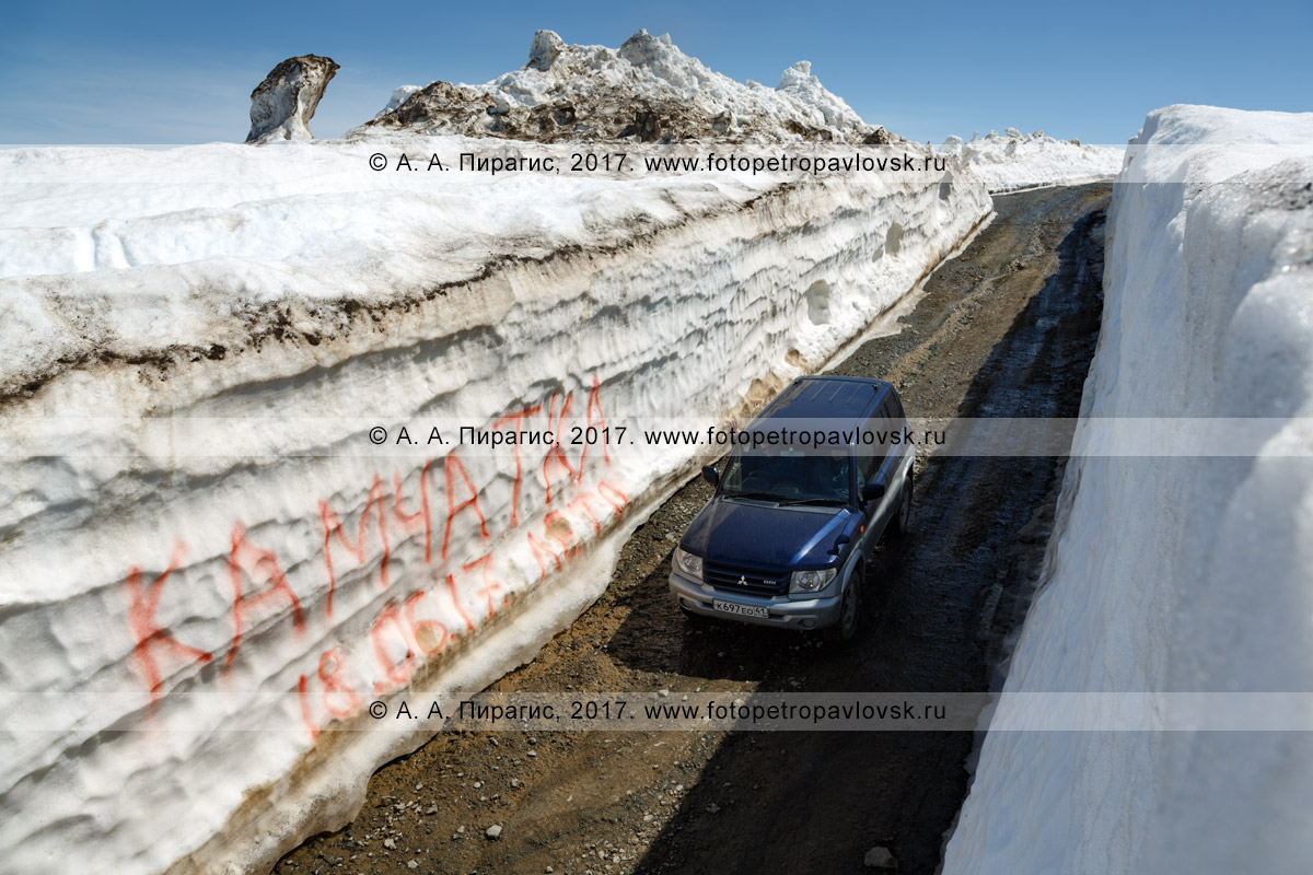 Фотография: японский полноприводный автомобиль Mitsubishi Pajero iO едет по горной дороге через многометровый снежный тоннель на Вилючинском перевале на полуострове Камчатка