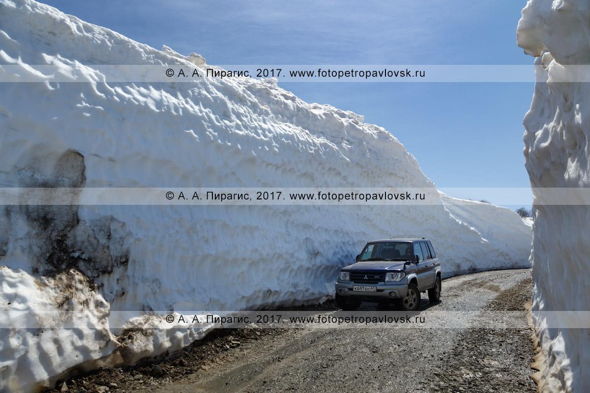 Фотография: полноприводный японский автомобиль Mitsubishi Pajero iO на горной дороге в узком многометровом снежном тоннеле на Вилючинском перевале в Камчатском крае