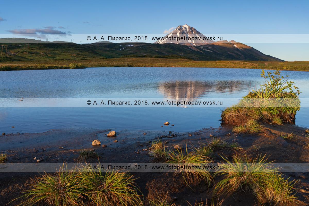 Фотография: берег высокогорного озера, вид на альпийские луга и конус Вилючинского вулкана на полуострове Камчатка