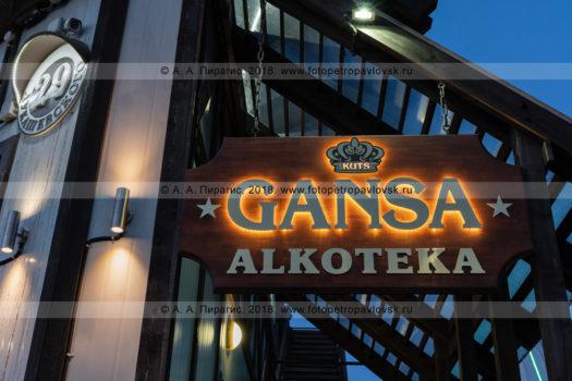 Ночная фотография деревянной вывески Gansa Alkoteka