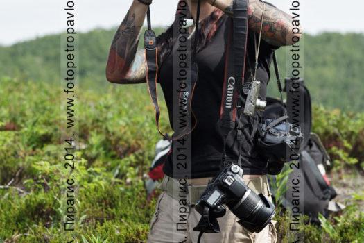 Девушка-туристка фотографирует на лоне дикой природы полуострова Камчатка