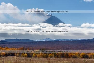 Фотография: вид на вулкан Ключевская сопка, находящийся в стадии извержения. Красивый осенний пейзаж полуострова Камчатка