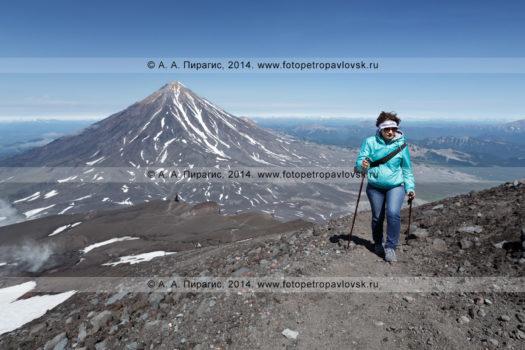 Фотография девушки поднимающейся на вершину Авачинского вулкана на фоне Корякского вулкана