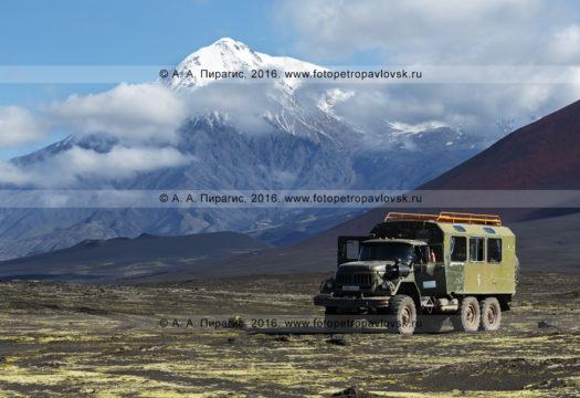 Фотография: туристический экспедиционный автомобиль высокой проходимости ЗИЛ-вахтовка припаркован, в ожидании туристов и путешественников, на Толбачинском долу на фоне вулкана Острый Толбачик. Полуостров Камчатка