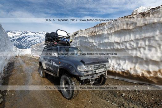 Фотография: японский полноприводный автомобиль Toyota Land Cruiser едет по горной дороге в многометровом снежном тоннеле на Вилючинском перевале на полуострове Камчатка